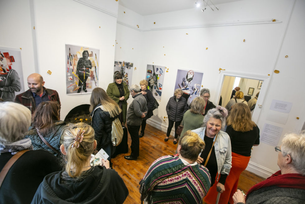 A crowd of people is standing in an exhibition room.