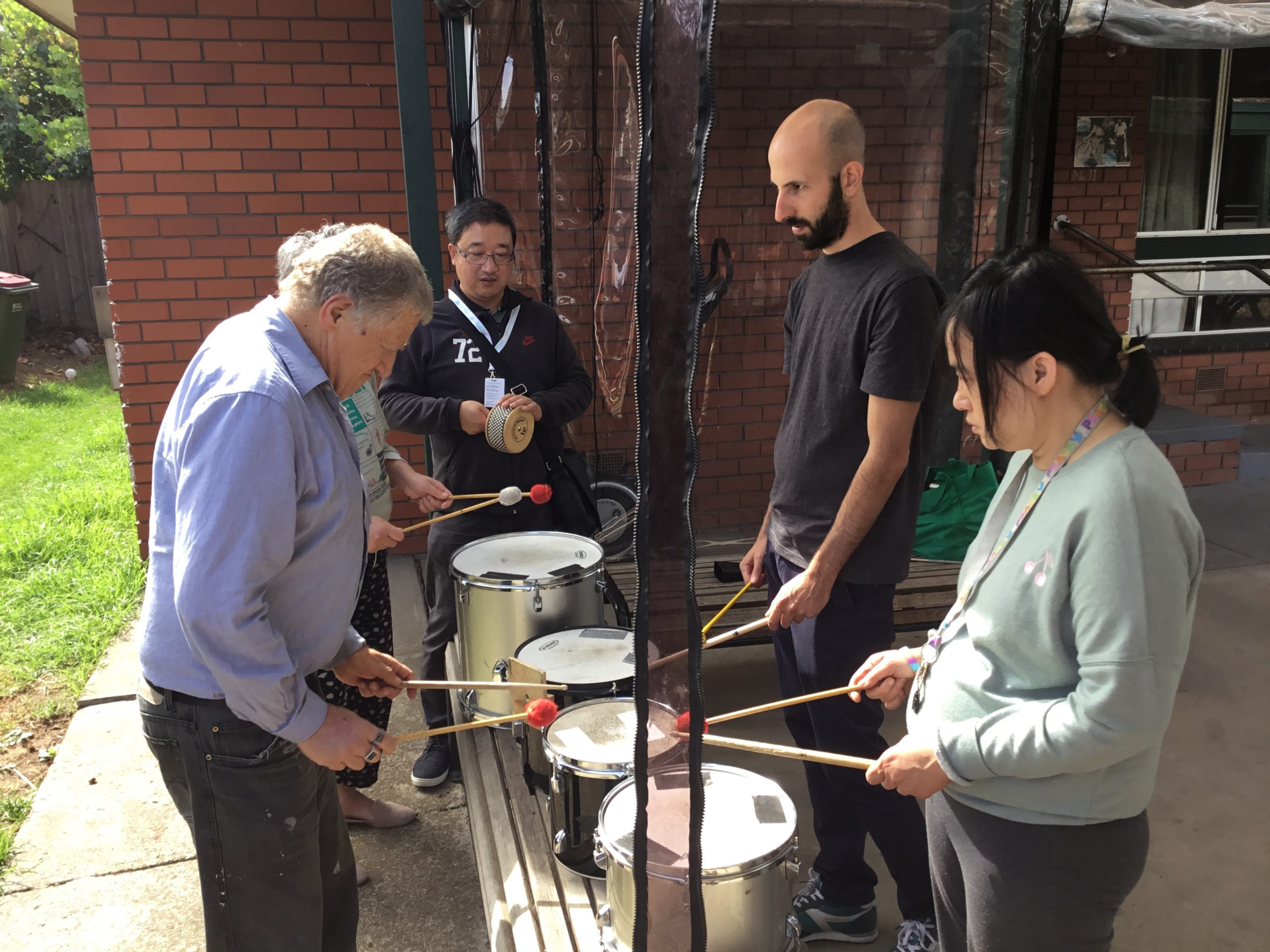 4 people are stand and playing the drums. While another person plays a Cabasa.