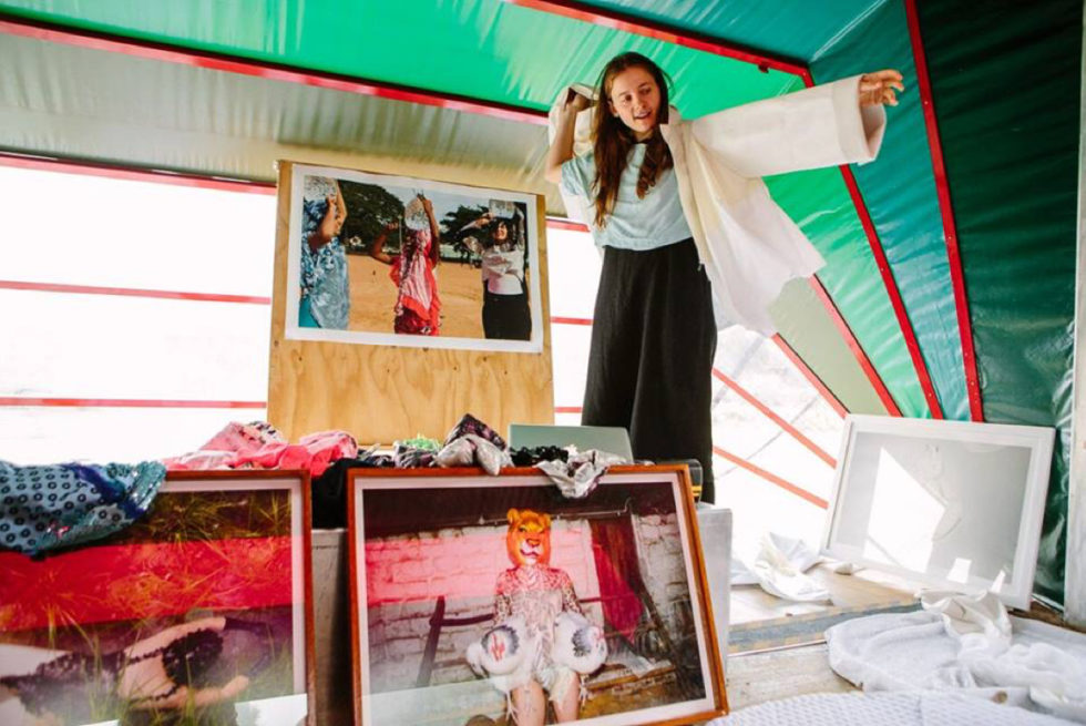 A person putting a jacket on inside Nebula, our portable arts space.