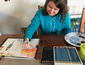 Emily sitting at their desk drawing with pencil colours on a piece of paper.