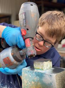 Robert using a silicone gun on a wooden sculpture.