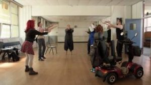 A group of people rehearsing with their hands up and in a circle.