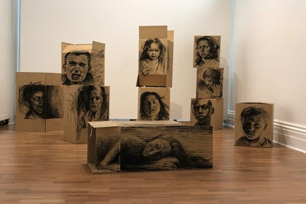 Cardboard boxes with drawings of people's faces on them.