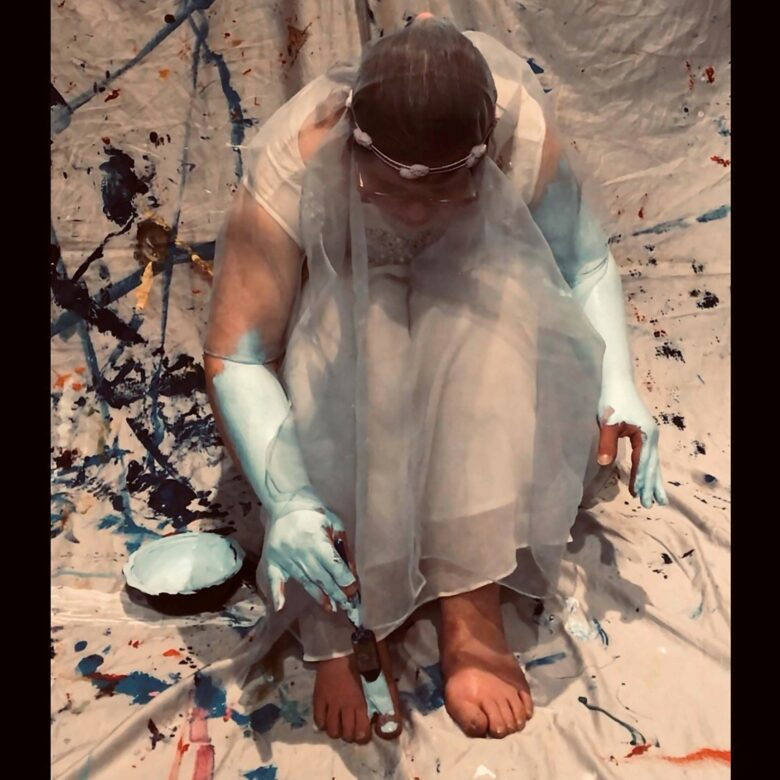Artist dressed in wedding dress, sits bent over her knees, painting her skin blue
