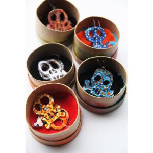 Dangaling Skull earrings in round boxes.