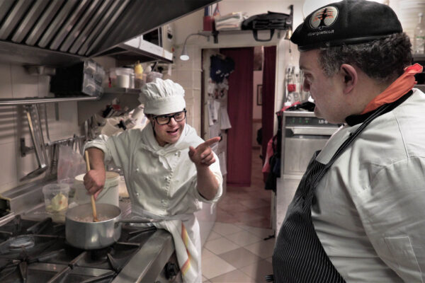 Two men are standing in a kitchen while one is pointing at the other.