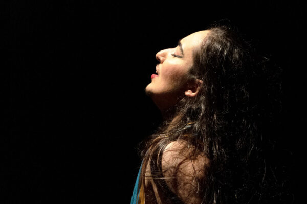 Raina Peterson, a person with long dark hair, stands in a darkened space, their face and shoulders illuminated by a theatre light. Their head is throw back and their mouth is slightly open, as if in a reverie.