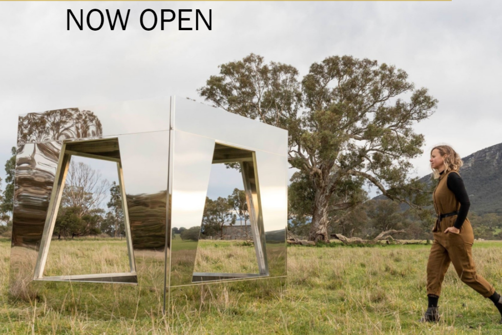 Large mirrored square sculpture in a grassy field with hills and trees in the background, a blond-haired woman in a brown jumpsuit walking towards it from the right. Writing say: Sustaining Creative Workers Initiative Now Open